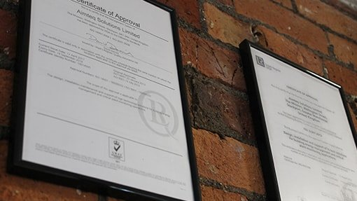 Accreditation - Aimteq certificates mounted on a brick wall