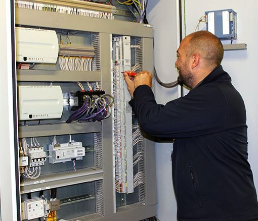 An Aimteq engineer investigating a BMS panel
