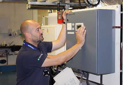 An Aimteq engineer performing maintenance tasks on a WEMS BEMS system